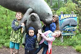kids posing by manatee statue - renew membership page