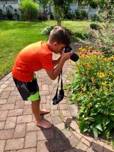 Boy photographing pollinator (Photo: Jessica Detrick)