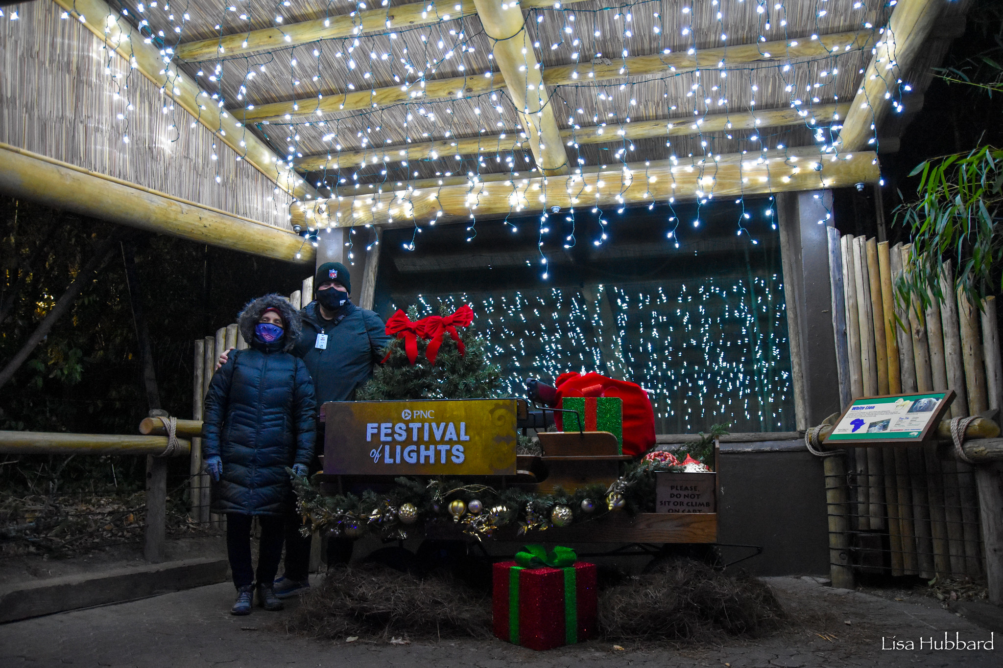 festival of lights couple standing by festival of lights sign